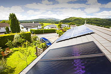 Solar thermal panels for heating hot water with solar PV electric panels behind on a house roof in Ambleside, Lake District, Cumbria, England, United Kingdom, Europe