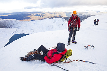 Climbers on the summit plateau of Helvellyn having just finished a route, looking down towards Red Tarn and Striding Edge, Lake District National Park, Cumbria, England, United Kingdom, Europe
