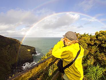 A woman photographs a double rainbow over Port Isaac, Cornwall, England, United Kingdom, Europe