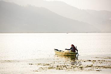 An old woman fishing on Phewa Lake, Pokhara, Nepal, Asia