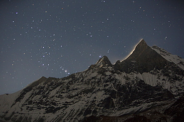 The night sky over Machapuchare with a glow from the moon rising behind the holy peak, Annapurna Sanctuary, Himalayas, Nepal, Asia