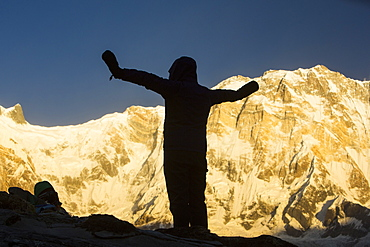 A trekker with alpenglow at sunrise on Annapurna South and Annapurna Fang, Nepalese Himalayas, Nepal, Asia