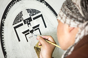 A Buddist artist painting a traditional Thanka painting at the Boudhanath Stupa, one of the holiest Buddhist sites in Kathmandu, Nepal, Asia