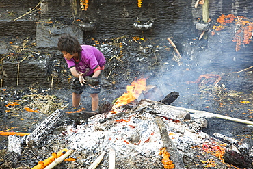Boy recycling wood after a cremation at the Pashupatinath Temple, a Hindu temple of Lord Shiva on the banks of the Bagmati River, UNESCO World Heritage Site, Kathmandu, Nepal, Asia
