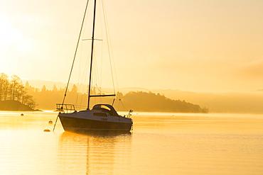 Sailing boats on Lake Windermere at sunrise with will o wisp mist, Waterhead, Ambleside, Lake District National Park, Cumbria, England, United Kingdom, Europe