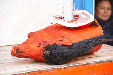 A dyed pig head on a butcher's shop slab in Kathmandu, Nepal, Asia