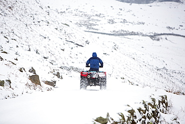 A farmer using a quad bike to get down Wrynose Pass, closed by winter snow, Lake District, Cumbria, England, United Kingdom, Europe