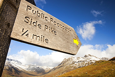 A footpath sign above Langale with the Langdale Pikes in the background, Lake District, Cumbria, England, United Kingdom, Europe