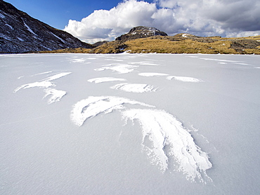 Wind drifted snow on Sprinkling Tarn at the head of  Borrowdale, frozen solid, looking towards Great End, Lake District, Cumbria, England, United Kingdom, Europe