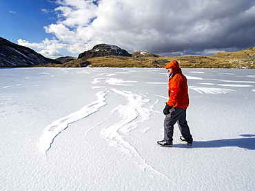 A climber on Sprinkling Tarn at the head of Borrowdale, looking towards Great End, with drifted snow making patterns on the ice, Lake District, Cumbria, England, United Kingdom, Europe