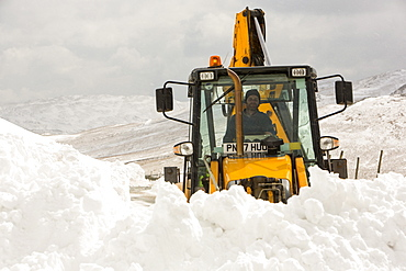 A JCB tries to clear a way through massive snow drifts blocking the Kirkstone Pass road above Ambleside in the Lake District, Cumbria, England, United Kingdom, Europe
