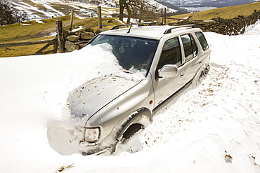 A four by four abandoned in massive snow drifts blocking the Kirkstone Pass road above Ambleside in the Lake District, Cumbria, England, United Kingdom, Europe