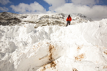 A walker on top of massive snow drifts blocking the Kirkstone Pass road above Ambleside, Lake District, Cumbria, England, United Kingdom, Europe