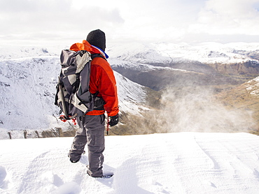 A walker on Gray Crag being battered by spindrift looking towards the Helvellyn rang during unseasonally cold weather in late March 2013, Lake District, Cumbria, England, United Kingdom, Europe