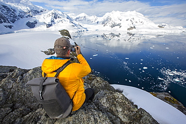 A passenger from an Antarctic cruise ship amongst stunning coastal scenery beneath Mount Walker in Paradise Bay off Graham Land on the Antarctic Peninsular. The Peninsular is one of the most rapidly warming places on the planet.
