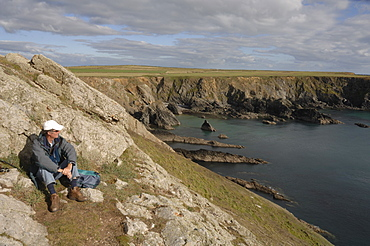 Man sitting on clifftop, looking out to sea, Deer Park, Martins Haven, Pembrokeshire, Wales, UK, Europe