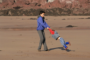 Mother spinning son around, West Dale beach, Dale, Pembrokeshire, Wales, UK, Europe