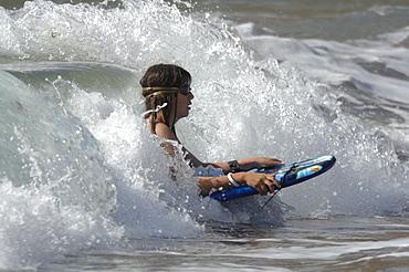 Girl boogie boarding on wave, West Dale beach, Pembrokeshire, Wales, UK, Europe