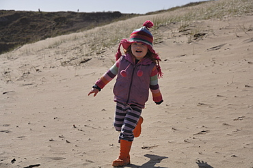 Young girl running in sand dunes,  Broad Haven South, Stackpole, Pembrokeshire, Wales, UK, Europe