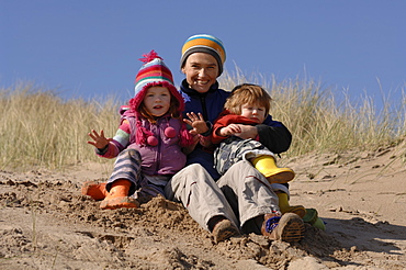 Mother and son and daughter playing in sand dunes, Broad Haven South, Stackpole, Pembrokeshire, Wales, UK, Europe