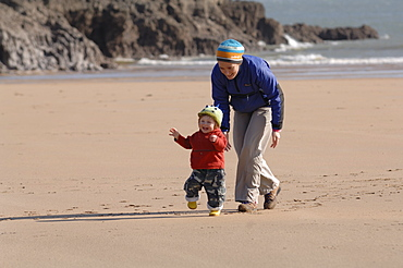 Mother and young son running on beach, Broad Haven South, Stackpole, Pembrokeshire, Wales, UK, Europe