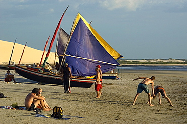 Tourists playing capoeira, traditional Brazilian martial arts and jangadas, typical Brazilian fishing boat, Jericoacoara Beach, Ceara, Brazil, South America