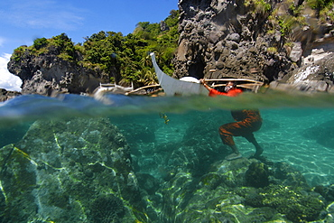 Fisherman wearing orange jumpsuit cleans his bangka, or traditional Philippino boat, Apo Island, Negros, Philippines, Southeast Asia, Asia