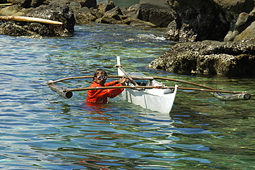 Fisherman wearing orange jumpsuit cleans his bangka (traditional Philippino boat), Apo Island, Negros, Philippines, Southeast Asia, Asia
