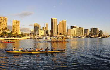 Young canoe rowers enjoy paddling near Ala Moana harbour at dusk, Waikiki, Oahu, Hawaii, United States of America, Pacific