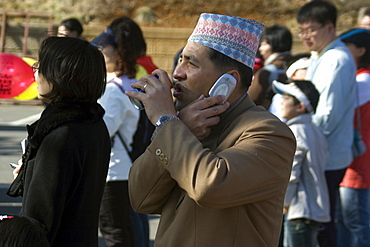 Nepalese drinking soda and talking on cell phone simultaneously, Geoje-Do, South Korea, Asia