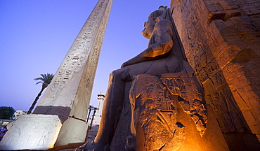 Obelisk and colossal statue of Rameses II on his thron, Luxor Temple. Luxor, Nile Valley, Egypt, Africa