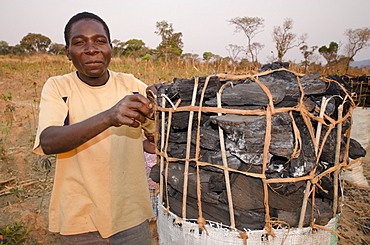 Charcoal maker selling charcoal on the side of the road, Zambia, Africa