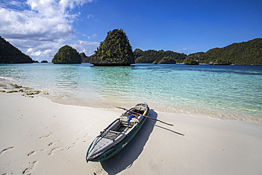 Karst limestone formations and lagoon in Wayag Island with the photographer's kayak, Raja Ampat, West Papua, Indonesia, Southeast Asia, Asia