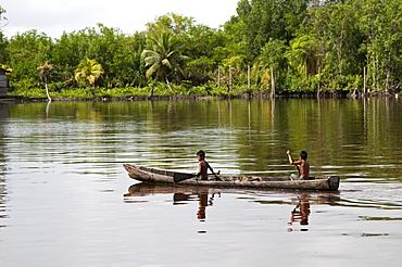Amerindian boys paddling dugout canoe, Maharuma, Guyana, South America