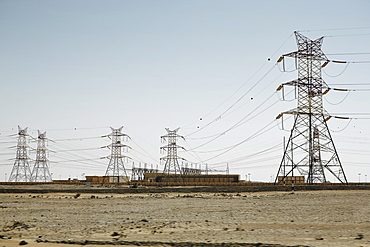 Electricity pylons dominate the flat barren landscape, pointing to civilisation somewhere, Qatar, Middle East