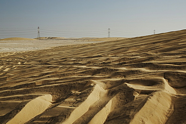 Sand dunes and electricity pylons dominate the desert landscape, Qatar, Middle East