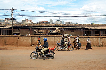 With the Kampala skyline appearing over the back wall of the Taxi park, pedestrians and motorcyclists share the roads.  Mopeds are a very popular and convenient form of transport around the City. . Kampala, Uganda, East Africa