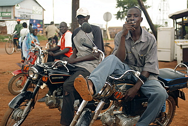In the North West of Uganda is Gulu District.  These bikers are relaxing between errands in the centre of Gulu town. Gulu Town, Uganda, East Africa