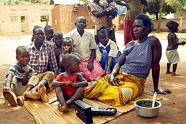 Time off from domestic chores and hard core playing, mothers rest in the shade with their children, listening to the radio. Gulu Town, Uganda, East Africa