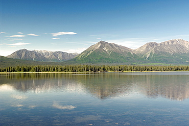Clear blue sky with thin fluffy clouds over mountain range in the Alaskan Interior, leading down to the water's edge.  Lake bordered by dense forrest. The Interior, Alaska, USA