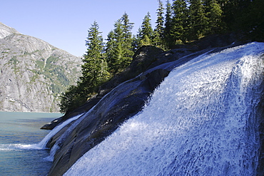 Glacier meltwater forms a small waterfall in Tracy Arm in southeast Alaska, USA.