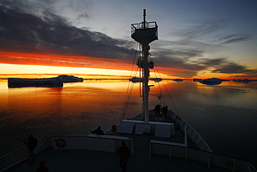 The National Geographic Endeavour cruises the Weddell Sea through icebergs at midnight near the Antarctic Peninsula.