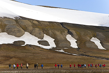 Hikers walking over open tundra beneath ice covered hills surrounding the Rosenberg Valley on EdgeØya Island in the Svalbard Archipelago in the Barents Sea, Norway.