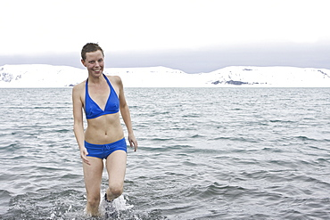 """Crew member Lisa Laegerstrom of the Lindblad Expedition ship National Geographic Endeavour taking the """"polar plunge"""" in Port Foster on Deception Island in the South Shetland Islands,  Antarctica."""