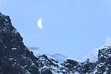 A waxing moon showing over snow covered cliffs in the Lemaire Channel on the west side of the Antarctic peninsula.