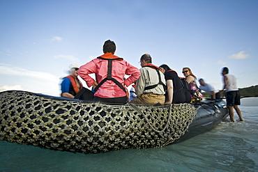 Lindblad Expeditions Guests boarding the Zodiac at Gardner Bay on Espanola Island in the Galapagos Island Archipeligo, Ecuador. No model releases.