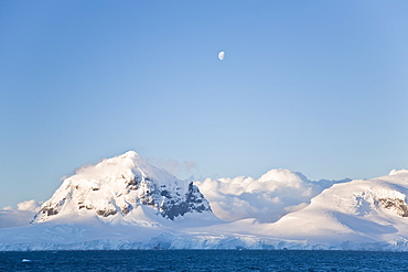 The Lindblad Expedition ship National Geographic Explorer in Dahlman Bay in late evening light as the waxing moon rises on the west side of the Antarctic Peninsula in Antarctica.