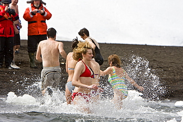 "Lindblad Expeditions guests doing the ""polar Plunge"" in Port Foster near Whalers Bay inside the caldera on Deception Island, South Shetland Island Group, Antarctica. NO MODEL RELEASES FOR THIS IMAGE."
