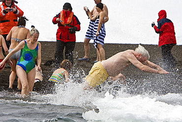 """Lindblad Expeditions guests doing the """"polar Plunge"""" in Port Foster near Whalers Bay inside the caldera on Deception Island, South Shetland Island Group, Antarctica. NO MODEL RELEASES FOR THIS IMAGE."""