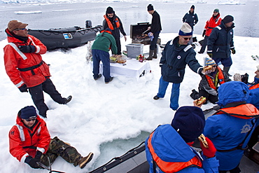 Guests from the Lindblad Expedition ship National Geographic Explorer enjoy a hot asado sandwich prepared by staff at BBQ on an ice floe near Adelaide Island, Antarctica